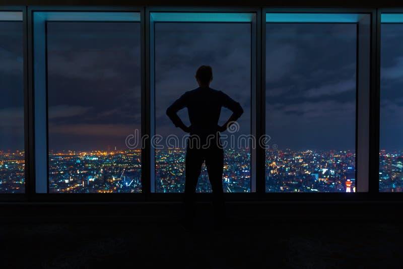 Man att se ut stora fönster som är höga ovanför en breda ut sigstad royaltyfri foto
