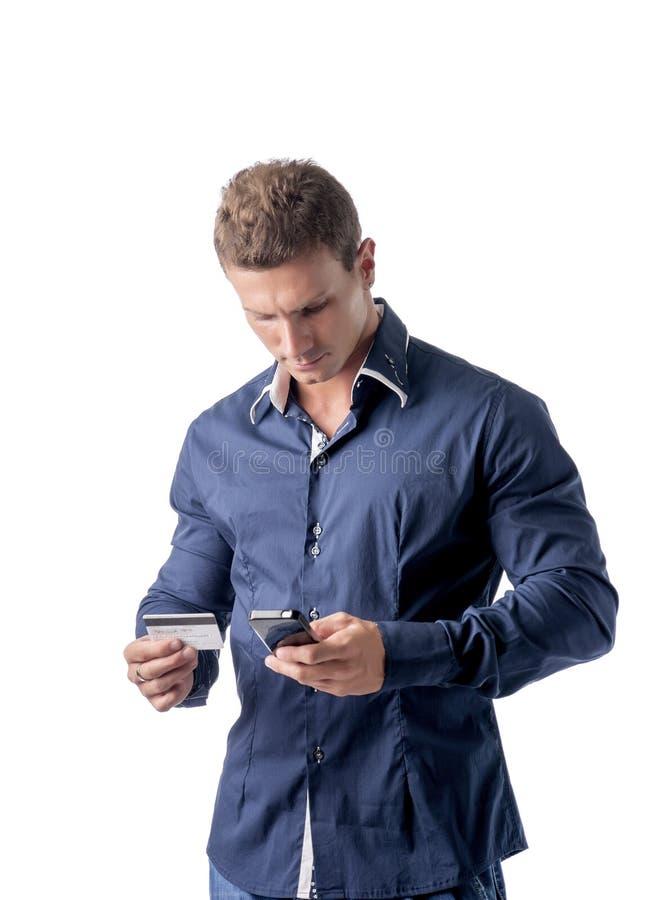 Man att shoppa direktanslutet på mobiltelefonen, hållande kreditkort arkivfoton