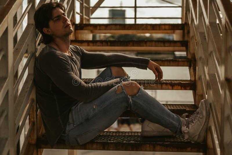 Man att sitta bara på trappuppgången och att se långt borta royaltyfri bild