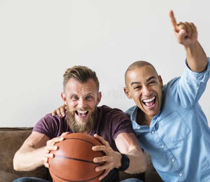 Man att sitta tillsammans på en hållande ögonen på sport för soffa arkivbild