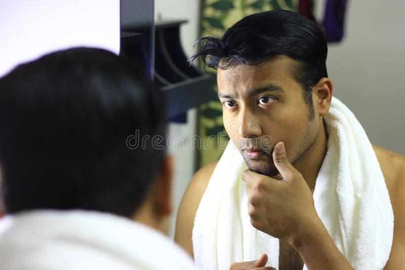 Man att sköta hans utseende framme av en spegelskönhet som utformar den lifestyleindian asiatiska mannen som in sköter hans utsee royaltyfria bilder