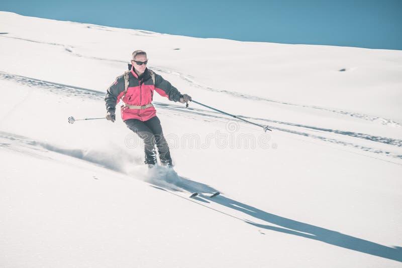 Man att skida av piste på snöig lutning i de italienska fjällängarna, med ljus solig dag av vintersäsongen Pulversnö med skidar s royaltyfria foton