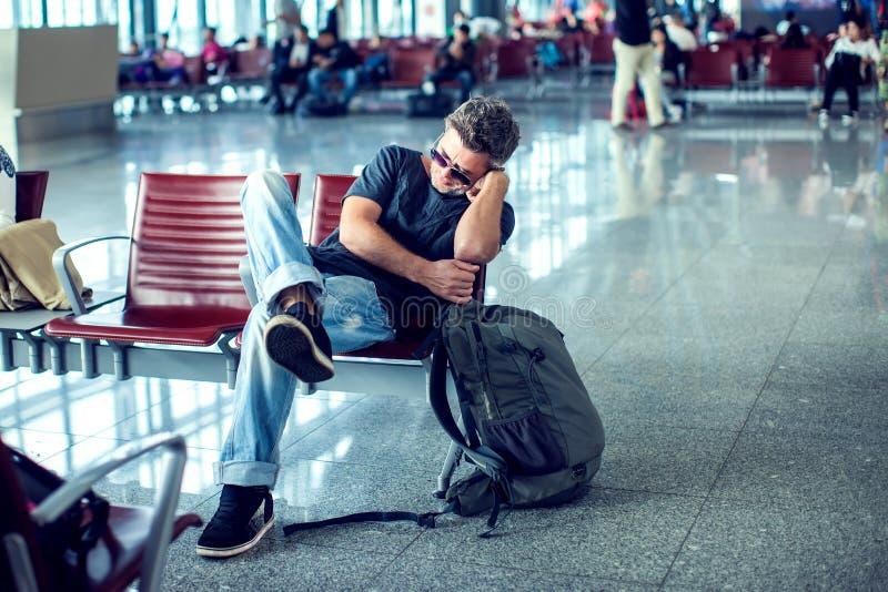 Man att sova, medan sitta i flygplatsterminal och väntande på f royaltyfria foton