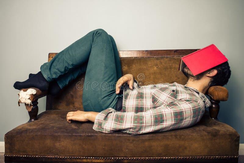 Man att sova på den gamla soffan med boken som täcker hans framsida arkivbild