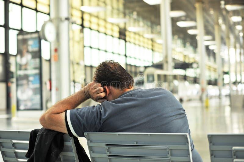 Man att sova på en bänk i järnvägsstationen fotografering för bildbyråer