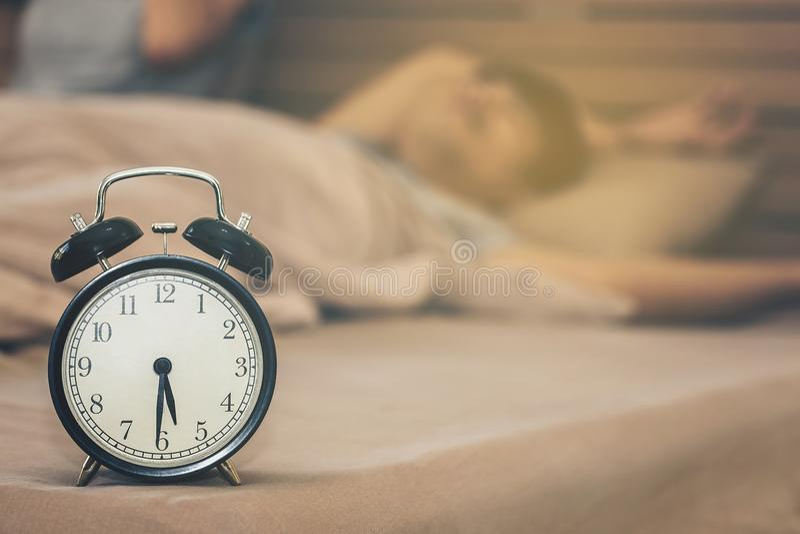 Man att sova, utan att vakna upp i morgonen med ringklockanolla royaltyfri foto