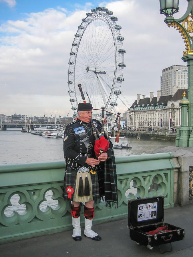 Man att spela den säckpipe- iklädda traditionella skotska dräkten på banker av flodThemsen royaltyfri fotografi