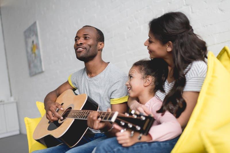 man att spela gitarren och att sjunga för fru och dotter royaltyfri bild