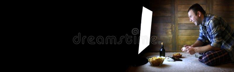 Man att spela på en konsol på styrspaken för den stora TVstenrans royaltyfri fotografi