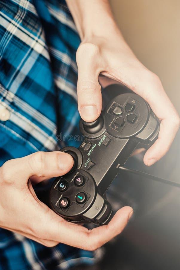 Man att spela på styrspaken i en modig konsol close upp royaltyfria foton