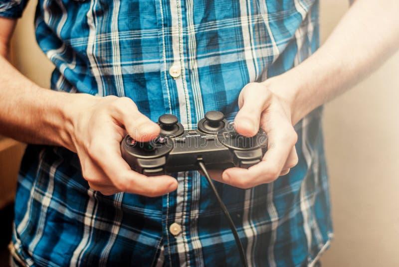 Man att spela på styrspaken i en modig konsol close upp arkivfoto