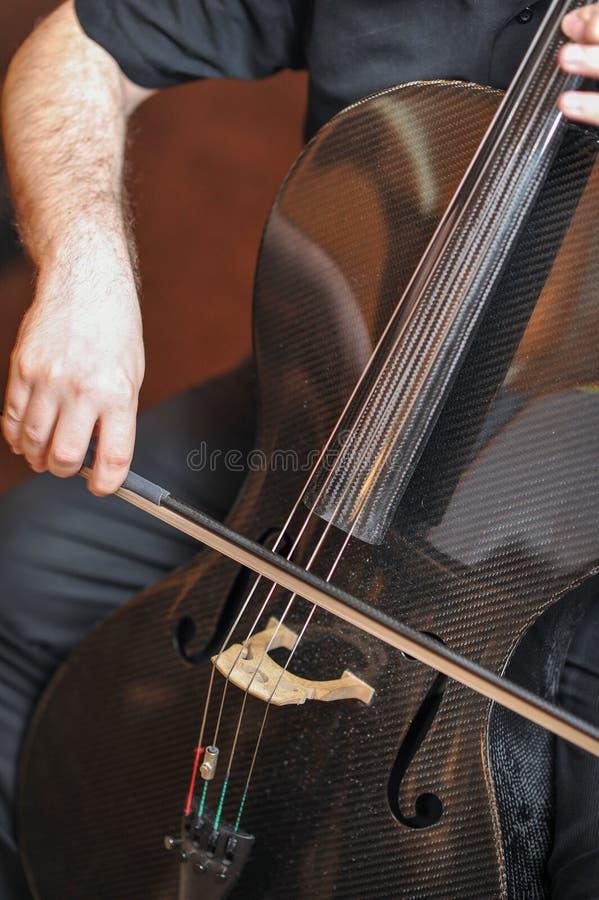 Man att spela violoncellen, nära övre för hand Violoncellorkestermusikinstrument som spelar musikern arkivfoton