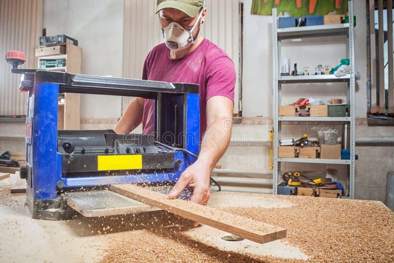 Man att spola ren ett träbräde på en thicknessing maskin fotografering för bildbyråer