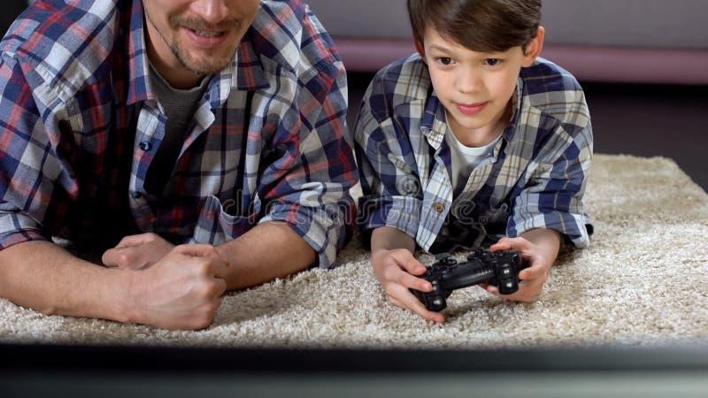 Man att stötta hans lilla son som hemma spelar videospelet, familjförhållandet arkivfoton
