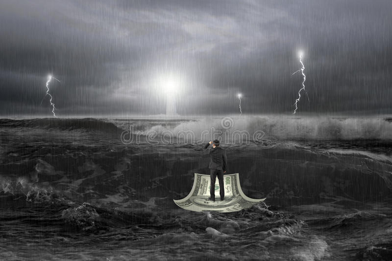 Man att stirra fyren på pengarfartyget i havet med stormen royaltyfria bilder