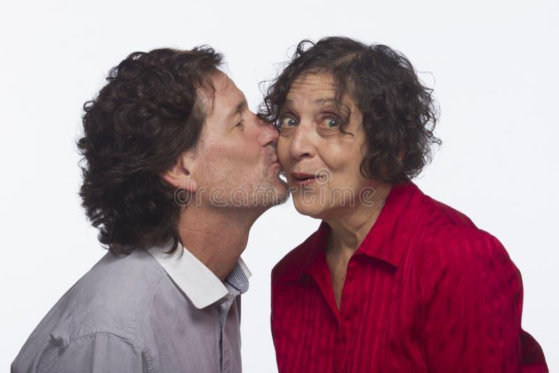Man att stjäla en kyss från kvinnan som är horisontal royaltyfria bilder