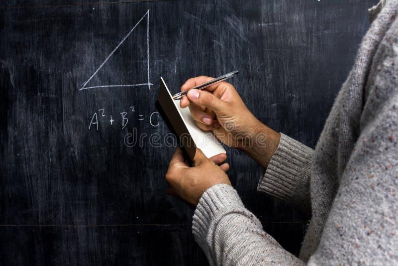 Man att ta anmärkningar av matematikteoremmen på svart tavla arkivbild