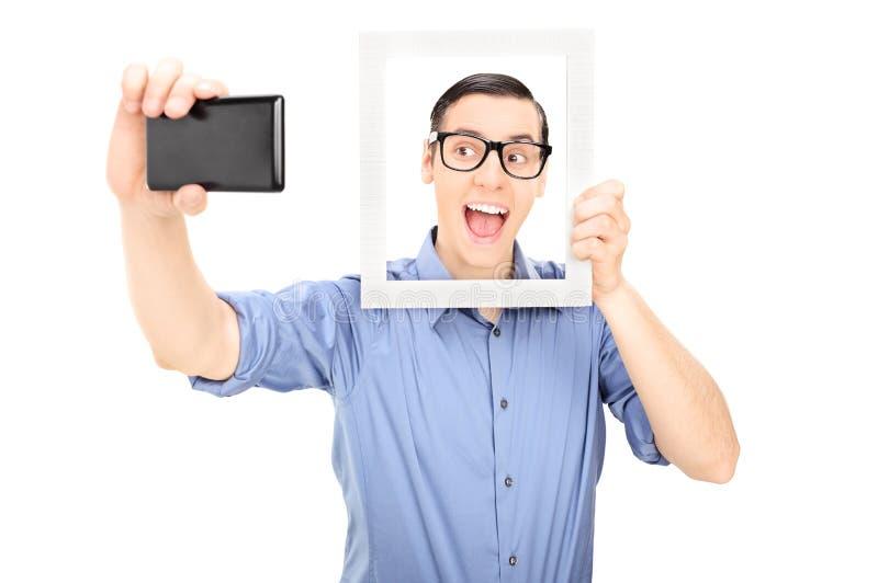 Man att ta en selfie och ett innehav en bildram royaltyfria bilder