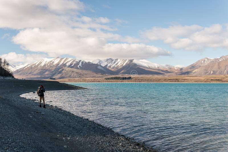 Man att ta ett foto av berg på sjön Tekapo royaltyfria bilder