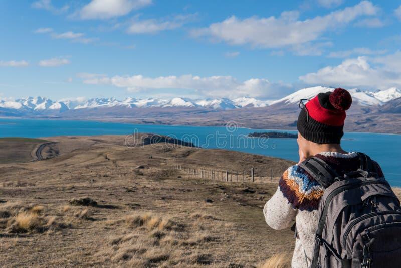 Man att ta ett foto av sjön Tekapo och snöa korkade berg royaltyfri foto