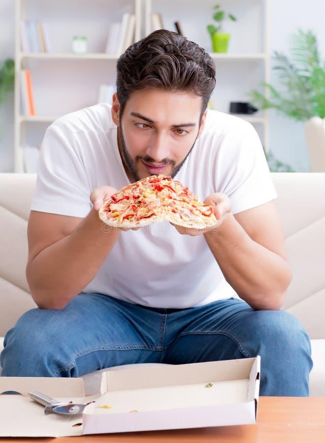 Man att ?ta pizza som har takeaway hemmastatt koppla av vila royaltyfria foton