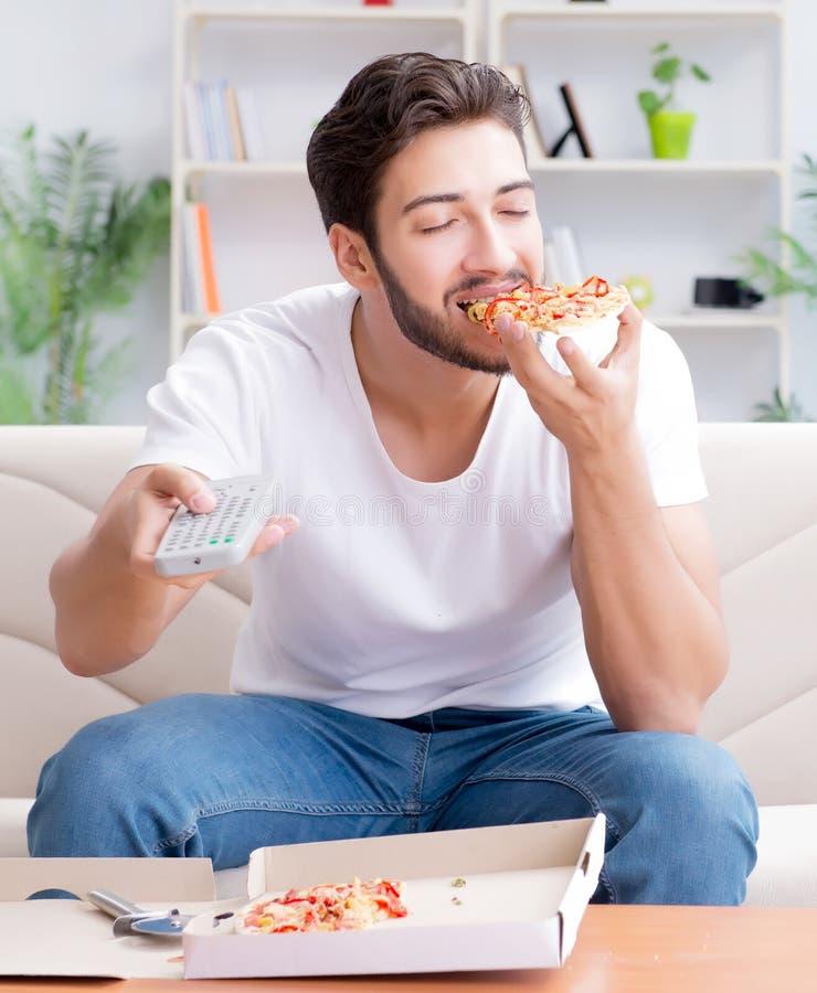 Man att ?ta pizza som har takeaway hemmastatt koppla av vila royaltyfria bilder