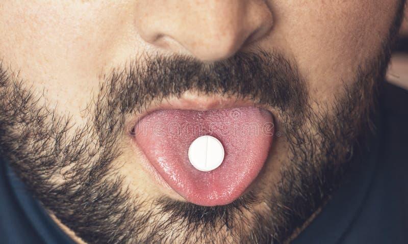 Man att ta preventivpilleren, minnestavlan av droger eller medicin på tungan med den öppna munnen Smärtstillande medelbehandling  fotografering för bildbyråer