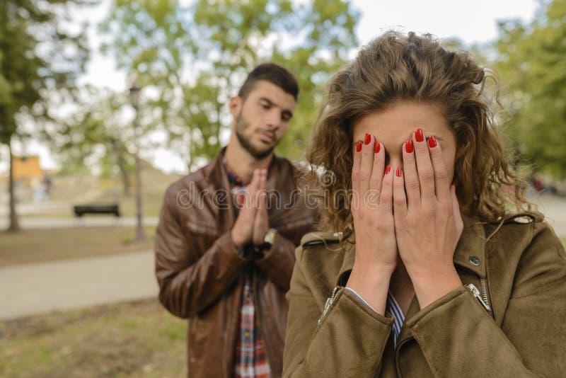 Man att tala till hans flickvän, medan hon gråter royaltyfria bilder