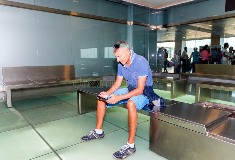 Man att vänta i flygplatsen som kopplar av med hans minnestavla royaltyfria bilder