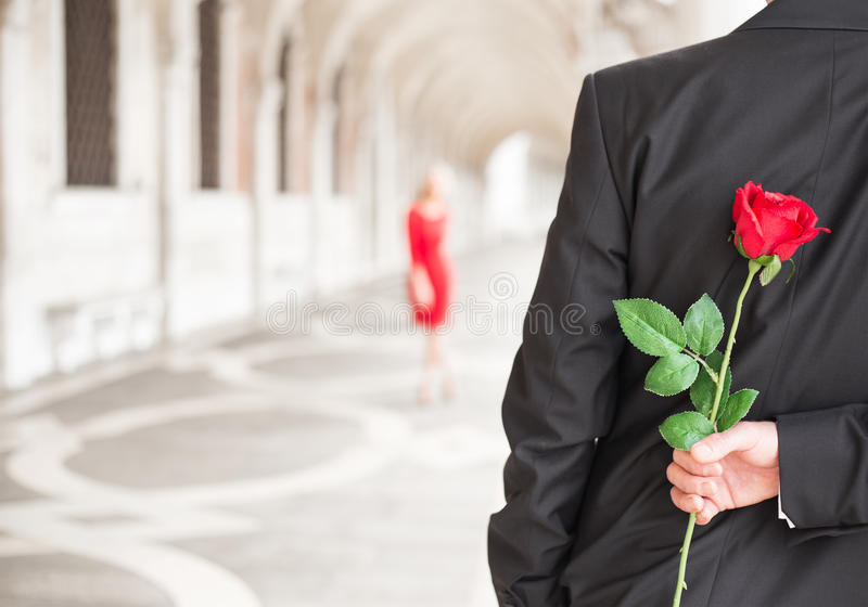 Man att vänta på hans datum med den röda rosen bak hans baksida royaltyfria foton