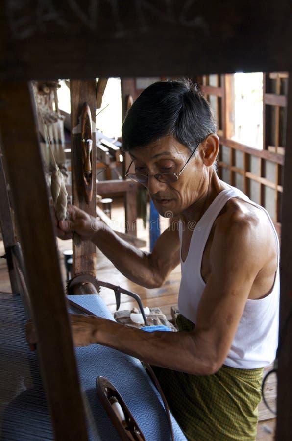 Man att väva silke vid handen på en maskin arkivbilder
