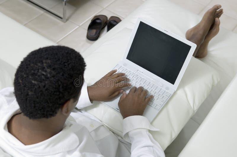Man att vila på soffan genom att använda sikt för hög vinkel för bärbar dator arkivfoton