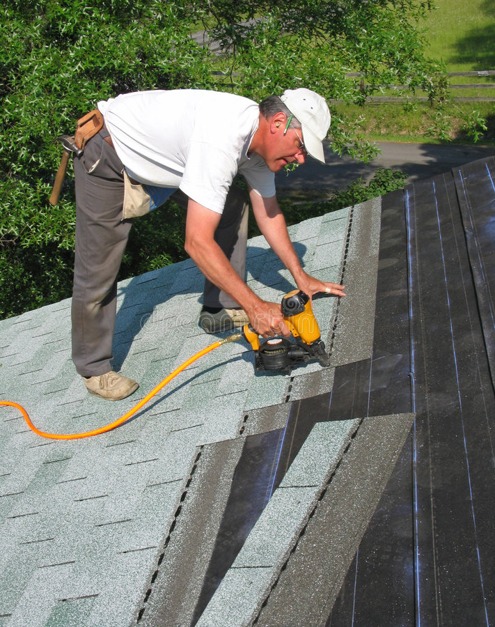 Free Man Attaches Shingles To Roof Stock Photos - 6014023