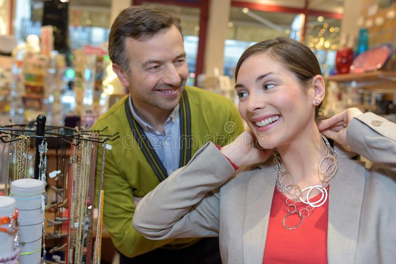 Man attaching necklace to girls neck in retail store royalty free stock image