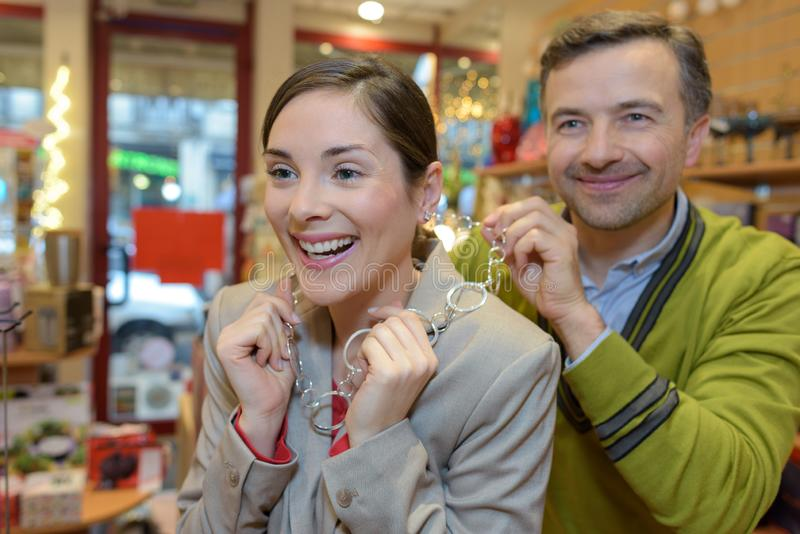 Man attaching necklace to girls neck in retail store stock photos