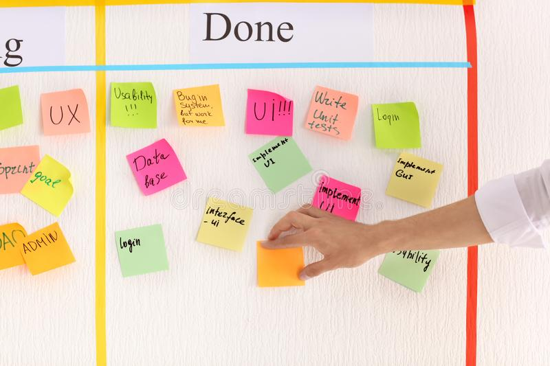 Man attaching sticky note to scrum task board in office royalty free stock photo