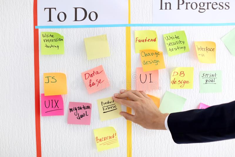 Man attaching sticky note to scrum task board in office royalty free stock photos