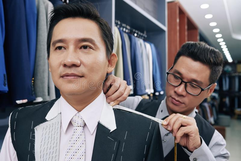 Man attending suit fitting royalty free stock photography