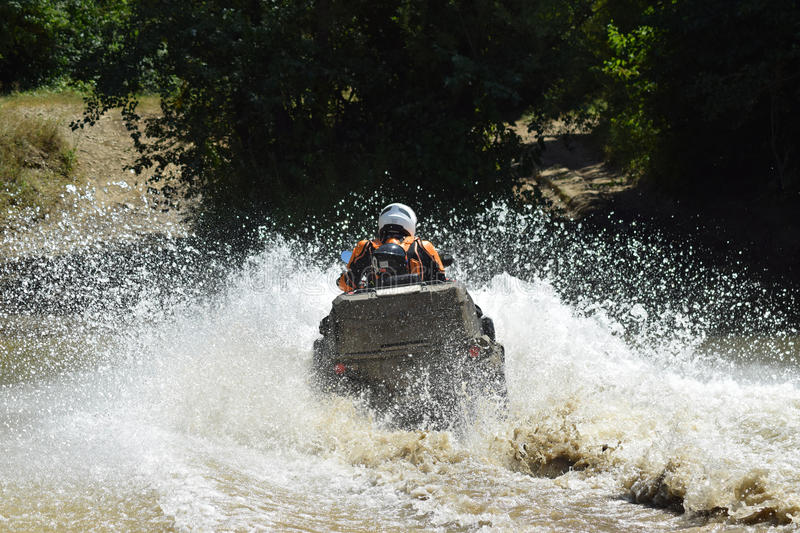 The man on the ATV crosses a stream royalty free stock photography