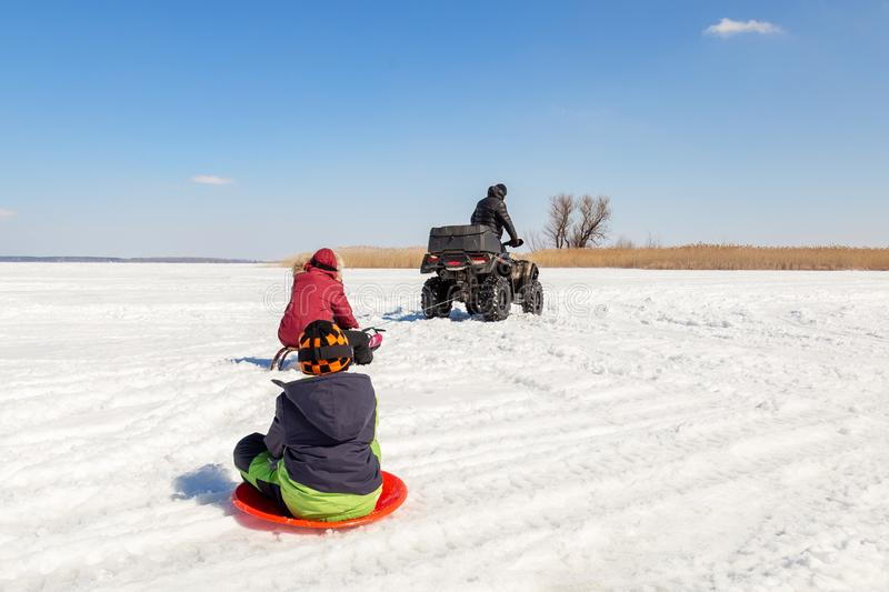 Man on ATV quadbike riding sledges with kids in tow on frozen lake surface at winter. Winter extreme sports and recreation. royalty free stock photo