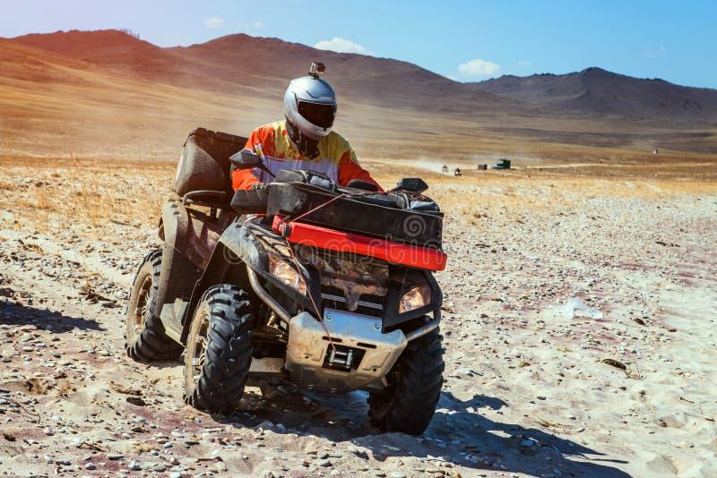 Man on ATV rides through the mountainside. On dry terrain royalty free stock photos