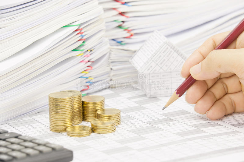 Man is auditing account with pencil and step gold coins stock photos