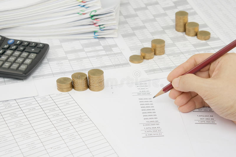 Man is auditing account by pencil with step gold coins royalty free stock photography