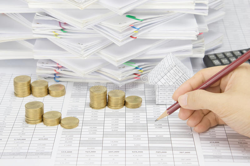 Man is auditing account by pencil with step gold coins stock photography