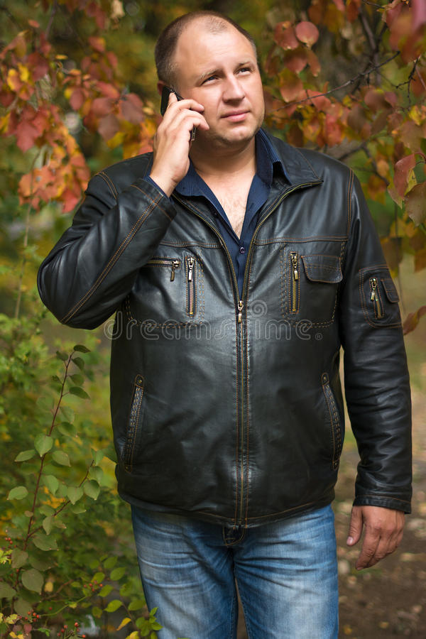Man in the autumn Park with phone stock photo