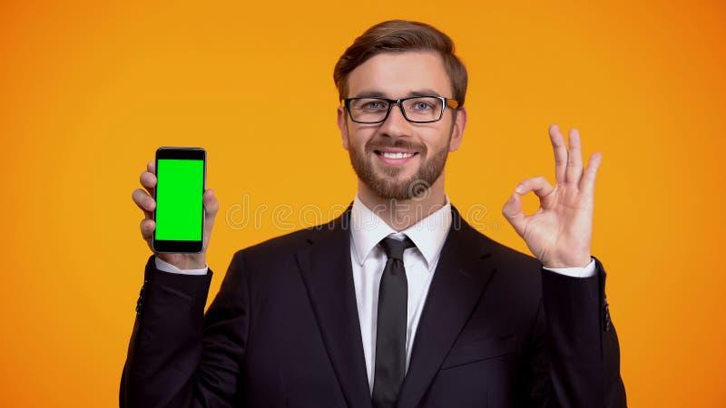 Man av aff?rsvisningsmartphonen med den gr?na sk?rmen och den ok gesten, kassa-baksida arkivfoton