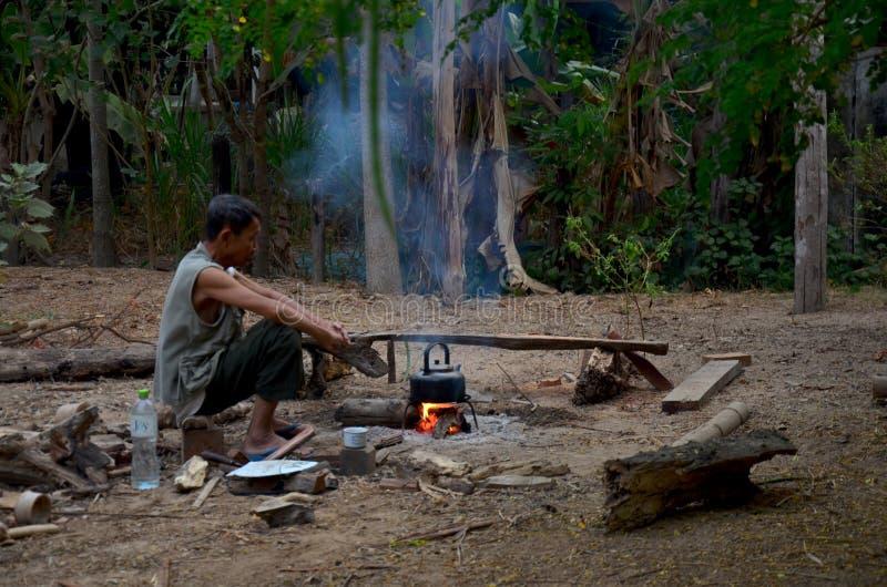 Man av Phu thai etniskt sammanträde på stammen och böldvattnet med royaltyfri fotografi