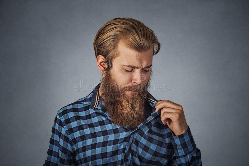 Man in awkward situation opening shirt to vent stock photography