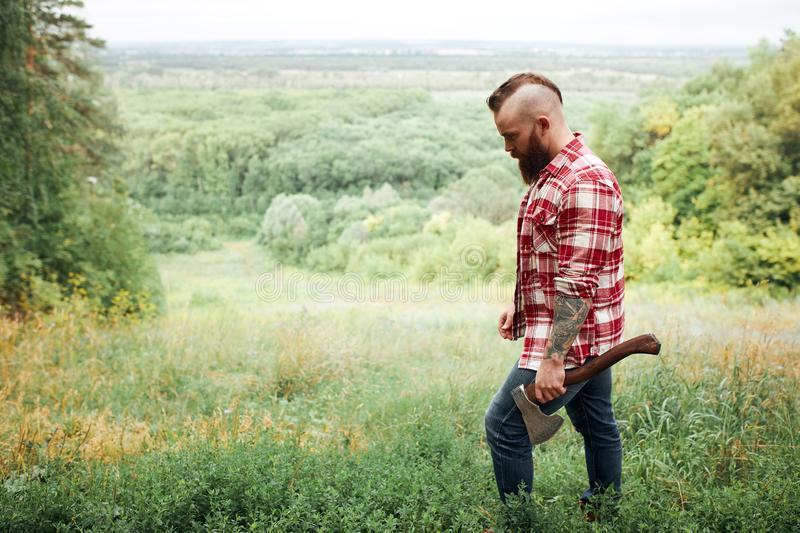 Man with axe, beard checkered shirt, lumberjack, nature background walks in forest. Man with axe, tired face and beard checkered shirt, lumberjack, nature royalty free stock image