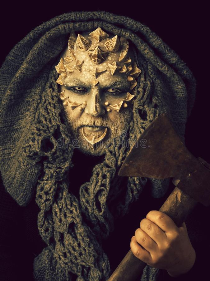 Man with axe in hand. Monster face with white eyes, thorns and warts. Demon head with grey hood on black background. Alien or evil creature with dragon skin stock photo